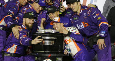 Denny Hamlin, center front, poses for a photo with his crew members after winning the NASCAR Daytona 500 auto race at Daytona International Speedway, Sunday, Feb. 17, 2019, in Daytona Beach, Fla