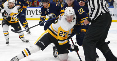 Buffalo Sabres forward Johan Larsson (22) and Pittsburgh Penguins forward Nick Bjugstad (27) battle after a faceoff during the second period of an NHL hockey game, Friday, March. 1, 2019, in Buffalo N.Y