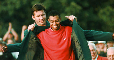 April 13, 1997, file photo, Masters champion Tiger Woods receives his Green Jacket from last year's winner Nick Faldo, rear, at the Augusta National Golf Club in Augusta, Ga. Woods completes an amazing journey by winning the 2019 Masters, overcoming 11 ye