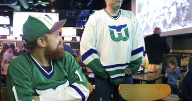 Scott St. Laurent, left, and Matthew Greene chat with other members of the Hartford Whalers Booster club, Thursday, May 9, 2019, at a restaurant in Manchester, Conn. They had gathered to watch Game 1 of the NHL Eastern Conference playoff series on between