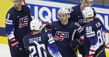 Patrick Kane of the US, left, scores his sides fifth goal past Sebastian Ylonen of France, right, and Jonathan Janil of France, center, during the Ice Hockey World Championships group A match between the United States and France at the Steel Arena in Kosi