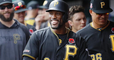 Pittsburgh Pirates' Starling Marte (6) celebrates in the dugout after hitting a two-run home run off Cincinnati Reds relief pitcher David Hernandez in the eighth inning