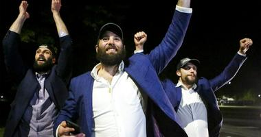 St. Louis Blues NHL hockey players Robert Bortuzo, left, Pat Maroon, center, and David Perron greet fans after arriving at the airport in St. Louis early Thursday, June 13, 2019.