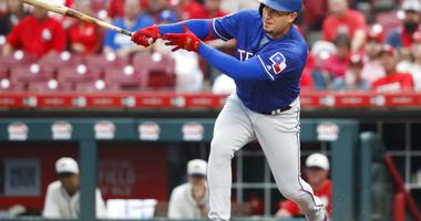 Texas Rangers' Asdrubal Cabrera hits an RBI single off Cincinnati Reds starting pitcher Tanner Roark during the first inning of a baseball game Saturday, June 15, 2019, in Cincinnati.