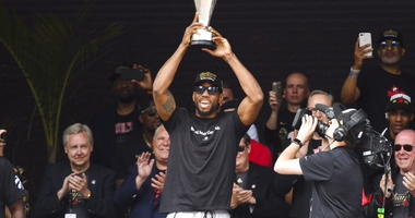 Toronto Raptors forward Kawhi Leonard hoists the MVP trophy next to teammates during the team's NBA basketball championship parade in Toronto, Monday, June 17, 2019.