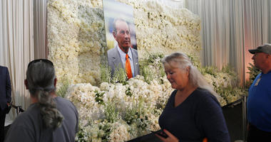 Fans file past a wall of flowers with a portrait of Denver Broncos owner Pat Bowlen placed in the center during a memorial Tuesday