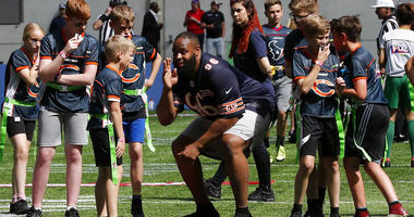 NFL Player Akiem Hicks of the Chicago Bears coaches a young team during the final tournament for the UK's NFL Flag Championship
