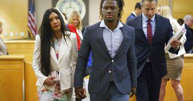 Philadelphia Phillies baseball player Odubel Herrera leaves a courtroom with his girlfriend, Melany Martinez-Angulo,
