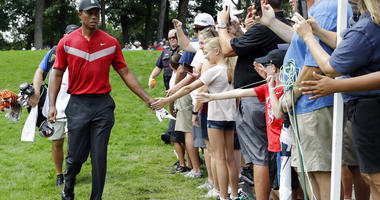 Tiger Woods, left, greets fans as he walks to the 14th fairway after hitting his tee shot during the final round of the BMW Championship golf tournament at Medinah Country Club, Sunday, Aug. 18, 2019, in Medinah, Ill.