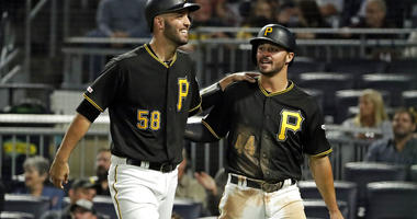 Pittsburgh Pirates' Kevin Kramer (44) and Jacob Stallings return to the dugout after scoring on a single by Erik Gonzalez off Chicago Cubs starting pitcher Kyle Hendricks during the seventh inning of a baseball game in Pittsburgh, Tuesday, Sept. 24, 2019.