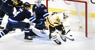 Pittsburgh Penguins' Zach Aston-Reese scores against Winnipeg Jets goaltender Laurent Brossoit