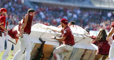 The Oklahoma Sooner Schooner flipped over during a touchdown celebration on the field during the first half of an NCAA college football game against West Virginia in Norman, Okla., Saturday, Oct. 19, 2019.