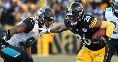 Pittsburgh Steelers running back Le'Veon Bell (26) carries the ball as Jacksonville Jaguars defensive end Yannick Ngakoue (91) chases in the AFC Divisional Playoff game at Heinz Field.