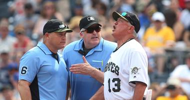 First base umpire Mark Carlson (6) and home plate umpire Bill Welke (middle) listen to Pittsburgh Pirates manager Clint Hurdle (13) after Hurdle is ejected during the eighth inning