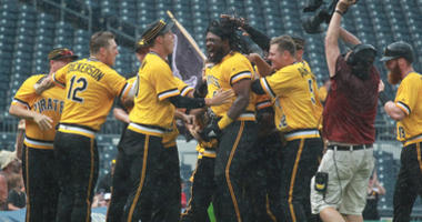 Pittsburgh Pirates first baseman Josh Bell (middle) is mobbed by teammates after driving in the game winning run against the Milwaukee Brewers during the tenth inning at PNC Park. Pittsburgh won 7-6.