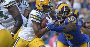 Green Bay Packers running back Aaron Jones (33) is defended by Los Angeles Rams linebacker Mark Barron (26)