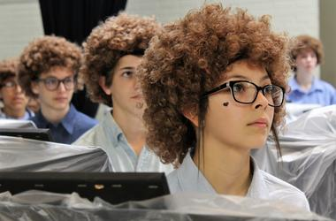 Ariceli, wearing her Bob Ross wig, listens to the artist speak on a video screen before painting began Thursday at Madison Middle School on Flash Bob Flash Mob Day.