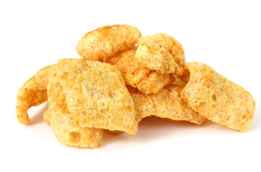Several barbecue seasoned pork rinds on a white background.