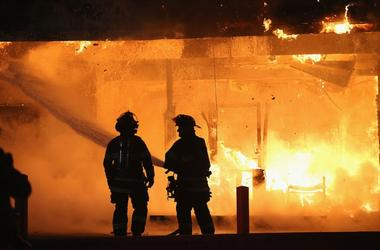 fire fighters stand in front of blazing building