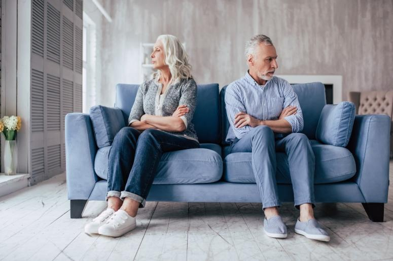 Couple sitting on couch facing away from each other