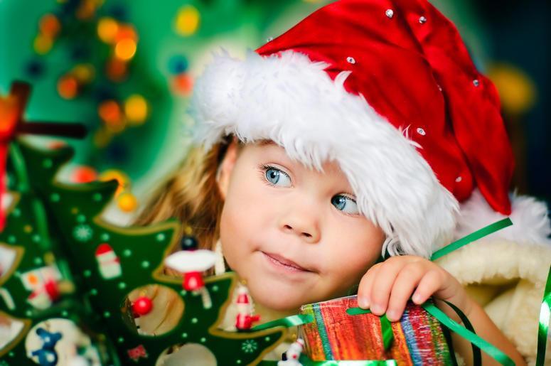 Happy small girl in Santas hat has a Christmas