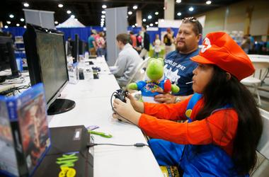 Natalie Menjibar, 9, is watched by her father, Jose, while playing a video game at the 5th Annual Game On Expo at the Phoenix Convention Center on Aug. 11, 2019. Game On Expo