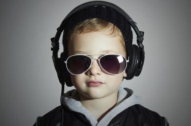 Little boy listens to music through headphones