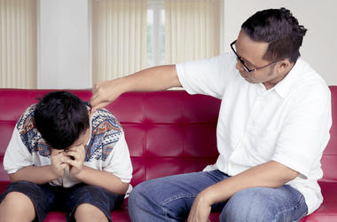father punishing his son at home