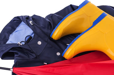 Rain gear Raincoat and umbrella and rubber boots on a white background. Protective, footwear. (Photo credit: Tetiana Rozhnovska/Dreamstime)