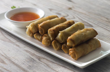 Philippine Lumpia Spring Rolls with spicy sauce on Wooden Table in Restaurant (Photo credit: Wong Yu Liang/Dreamstime)