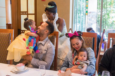 ANAHEIM, CALIFORNIA - APRIL 12: In this handout image, John Legend, Chrissy Teigen, their daughter Luna and son Miles share a moment with Princess Tiana during the Disney Princess Breakfast Adventures at Disney's Grand Californian Hotel on April 12, 2019