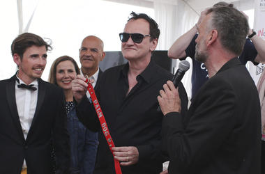 Director Quentin Tarantino poses for photographers with the Palm Dog collar award