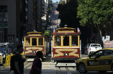A cable car at right begins to make its way up California Street Wednesday, Sept. 11, 2019, in San Francisco. (AP Photo/Eric Risberg)