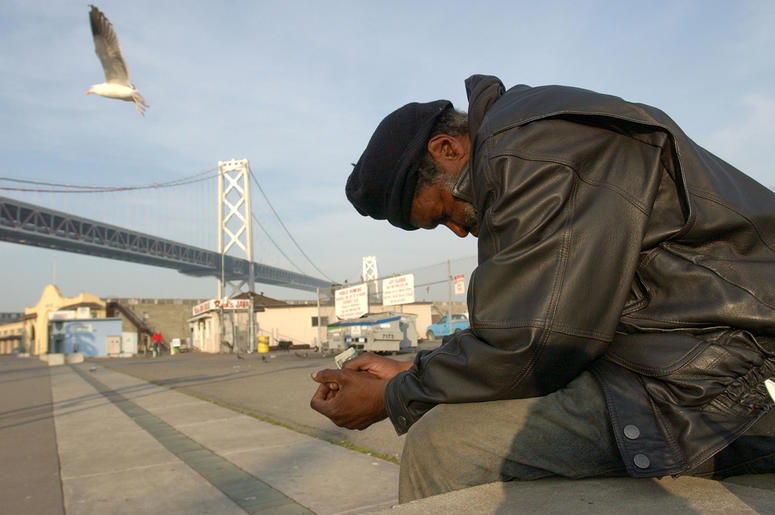 SAN FRANCISCO, CA - DECEMBER 5: Maceo Grigsby, a homeless man, sits by the waterfront with the San Francisco Bay Bridge in the background December 5, 2002 in San Francisco, California. San Francisco has attracted increasing numbers of homeless people in r