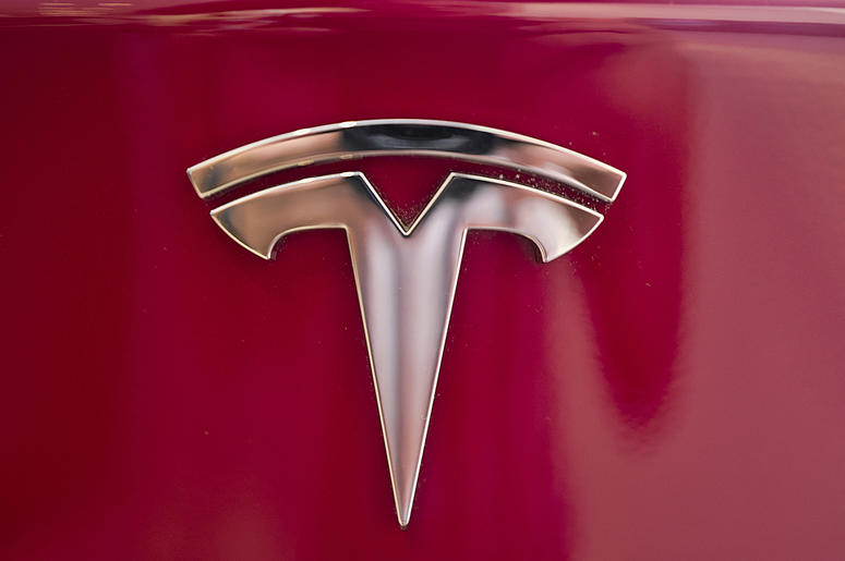 This Wednesday, Aug. 8, 2018, file photo shows the Tesla emblem on the back end of a Model S in the Tesla showroom in Santa Monica, Calif. The California Highway Patrol says it may have used the Autopilot system of a Tesla Model S to stop the car after it