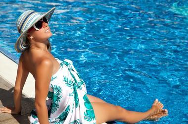 Luxury resort woman in sarong relaxing in swim pool. Beautiful female model enjoying sun.