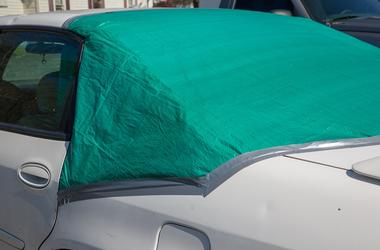 Green tarp covers back window to protect from the elements