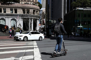 Guy rides motorized scooter through metro area.