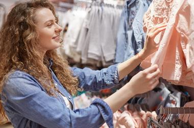 Satisfied glad female with curly hair wears fashionable clothing, chooses new blouse in shopping centre, pays attention on quality