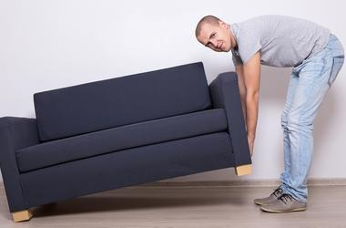Young man lifting up sofa or couch