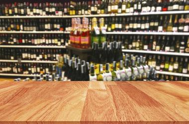 Wood table and wine Liquor bottle on shelf blurred background. Label, display.