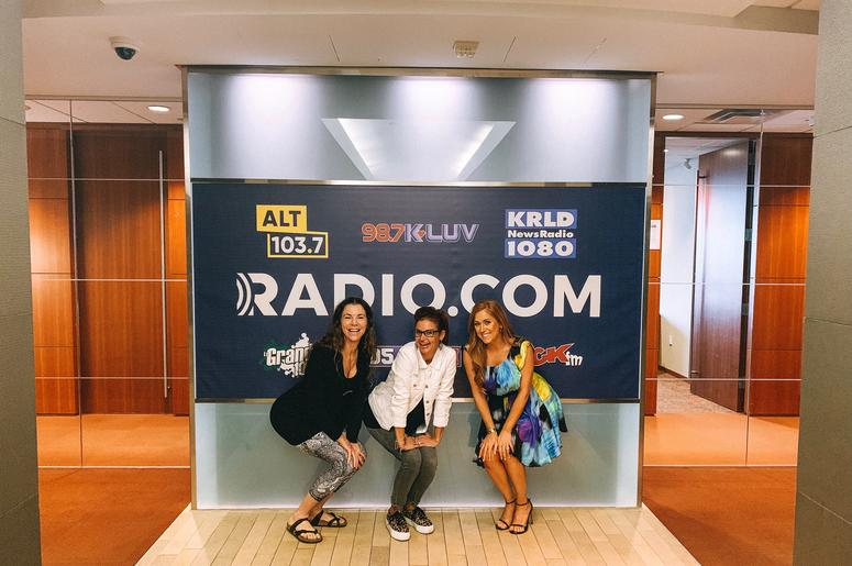 Tyler Dawn, Sybil Summers, and Hilary Kennedy pose in front of RADIO.COM sign