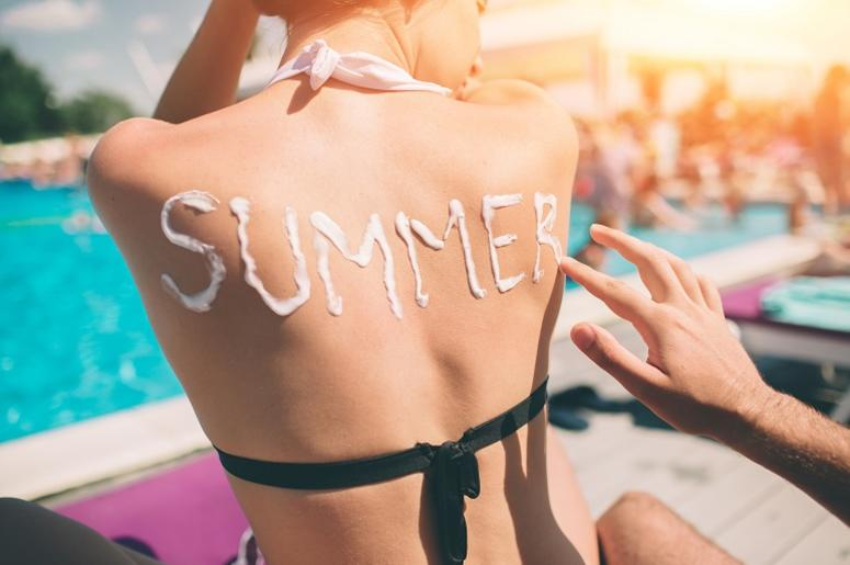 Summer concept. Man writing the word Summer on a woman`s back. Man applying sunscreen on the skin of a girl.