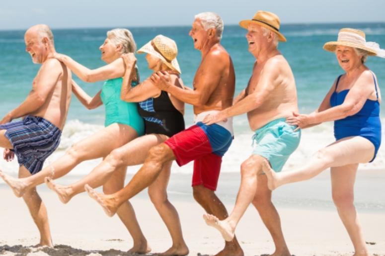 Seniors dancing in a row at the beach