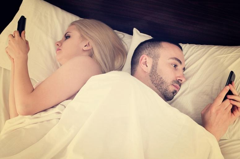 Couple socializing with mobile phones in bed