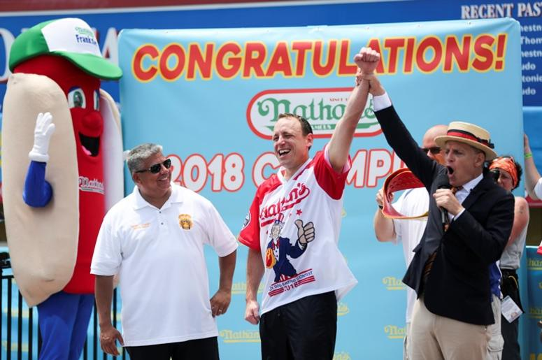 Joey Chestnut (L) celebrates victory after winning men's division competition at the Nathan's Hot Dog Eating Contest at Coney Island of New York, the United States, July 4, 2018. American man Joey Chestnut set a new world record Wednesday by devouring 74