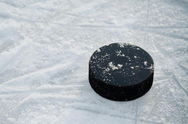 An ice hockey puck rests on the ice.