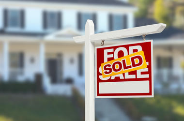 Home with sold sign in front of it