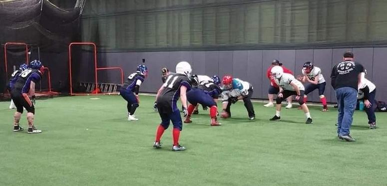 Female football players in full uniform line up for a practice play