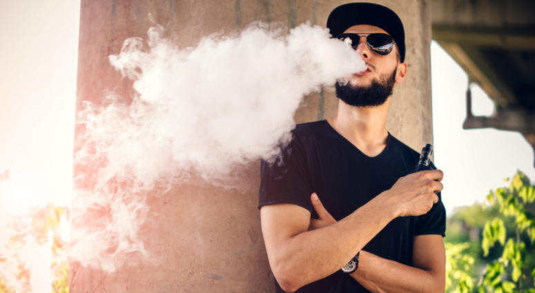 Young man blows huge cloud of steam from vaping device